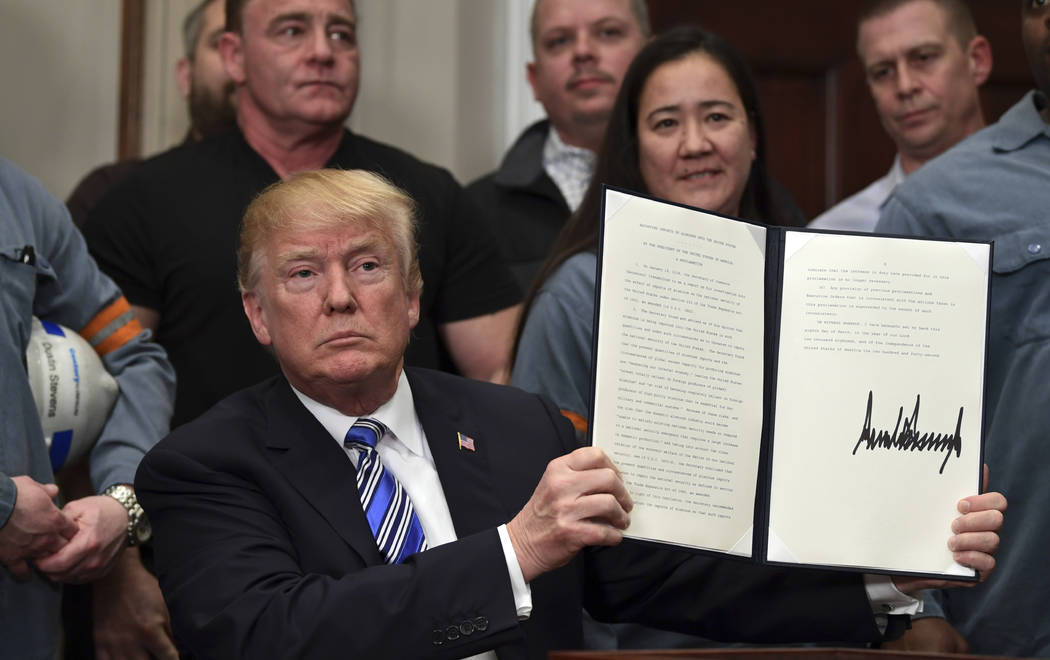 President Donald Trump holds up a proclamation on aluminum during an event in the Roosevelt Room of the White House in Washington, Thursday, March 8, 2018. He also signed one for steel. (Susan Wal ...