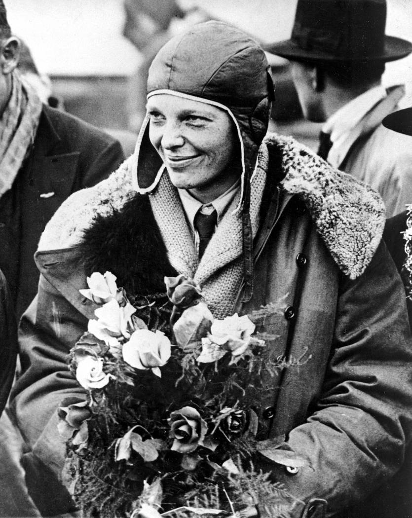 """FILE - In a June 26, 1928 file photo, American aviatrix Amelia Earhart poses with flowers as she arrives in Southampton, England, after her transatlantic flight on the """"Friendship"""" from  ..."""
