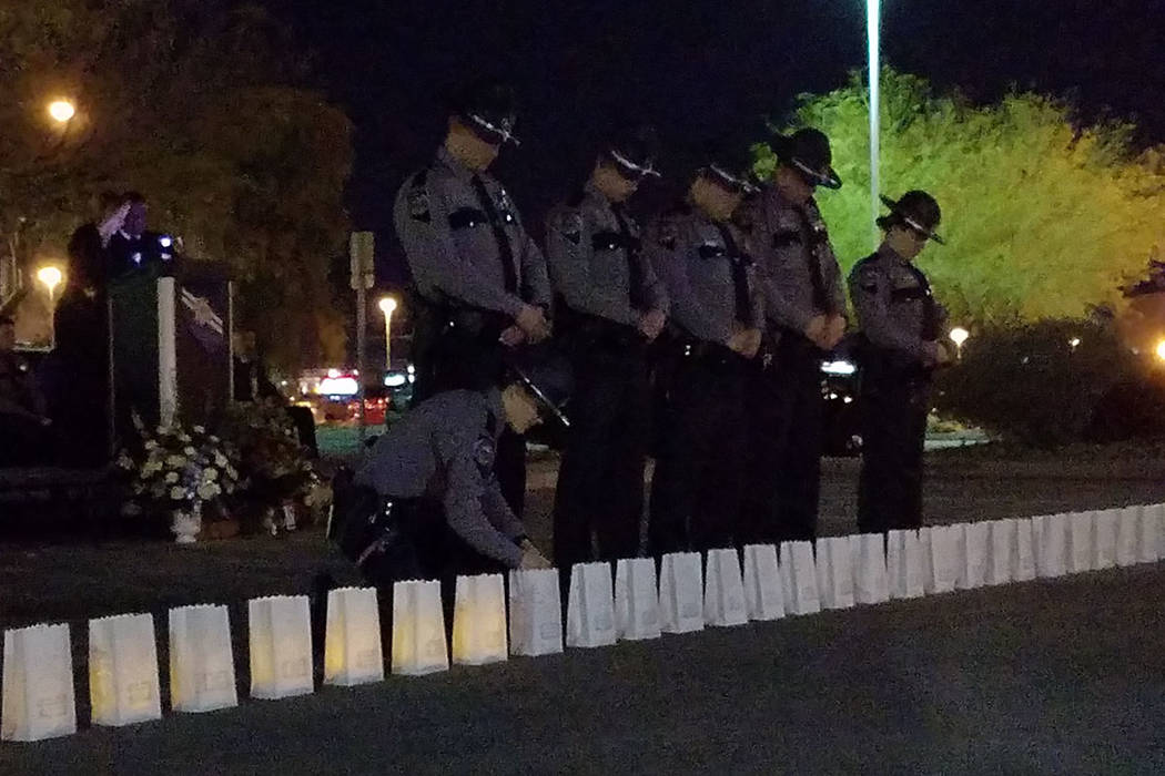 Nevada Highway Patrol troopers stand solemnly during a candlelight vigil at the Highway Patrol offices in Las Vegas on March 9, 2018. At a podium nearby, a woman reads names of 59 people who died  ...