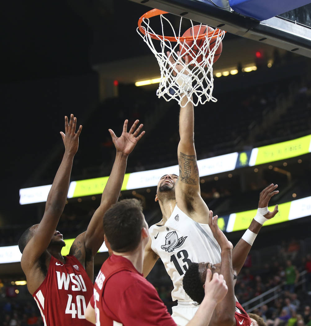 Oregon Ducks forward Paul White (13) sends up a shot as Washington State Cougars guard Kwinton Hinson (40) defends during the Pac-12 basketball tournament at T-Mobile Arena in Las Vegas on Wednesd ...