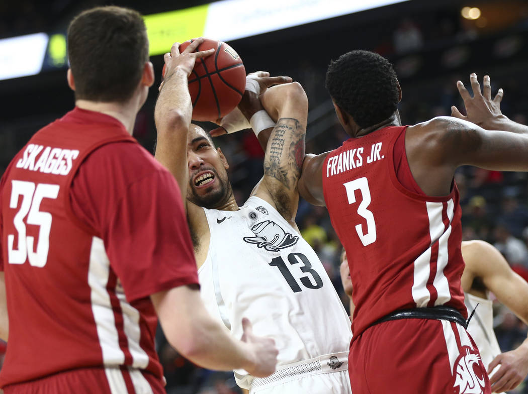 Oregon Ducks forward Paul White (13) tries to keep control of the ball as Washington State Cougars forward Robert Franks (3) defends during the Pac-12 basketball tournament at T-Mobile Arena in La ...