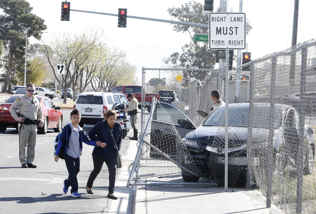 Las Vegas police investigate after a car crashed into a gate at Fyfe Elementary School after a two-vehicle collision near Valley View Boulevard and West Bonanza Road, Friday, March 8, 2018. (Bizua ...