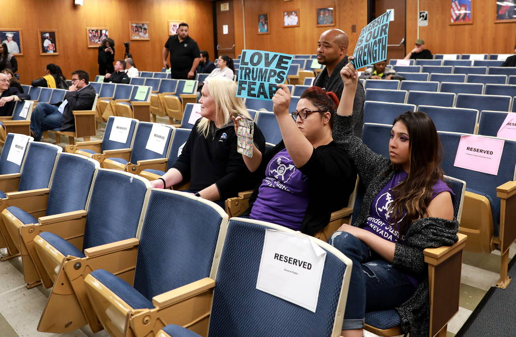 Laura Hernandez, center, and Kristina Hernandez, right, hold their signs up high after the majority of the crowd left following the Clark County School Board's decision to pull a controversial gen ...
