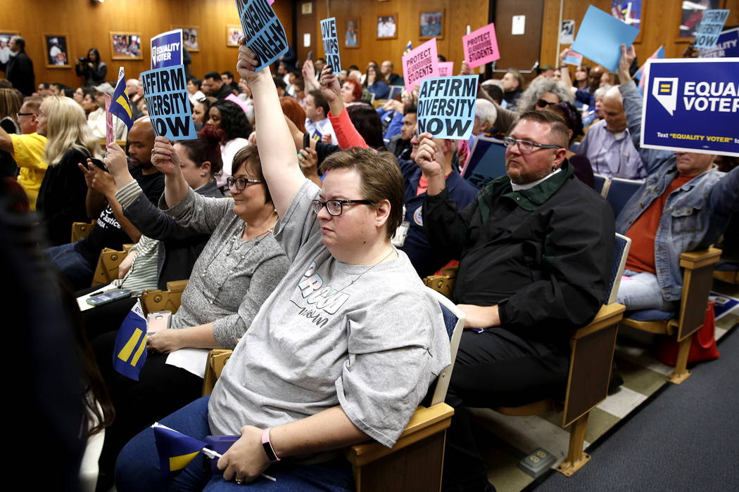 Attendees hold up signs during a Clark County School Board meeting, which ended with the board pulling a controversial gender-diverse policy from the agenda, at the Edward Greer building on Flamin ...