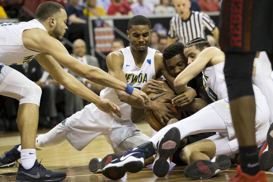 UNLV Rebels forward Shakur Juiston (10), second from right, fights for the ball against Nevada Wolf Pack players from left, Nevada Wolf Pack guard Kendall Stephens (21), guard Josh Hall (33) and f ...