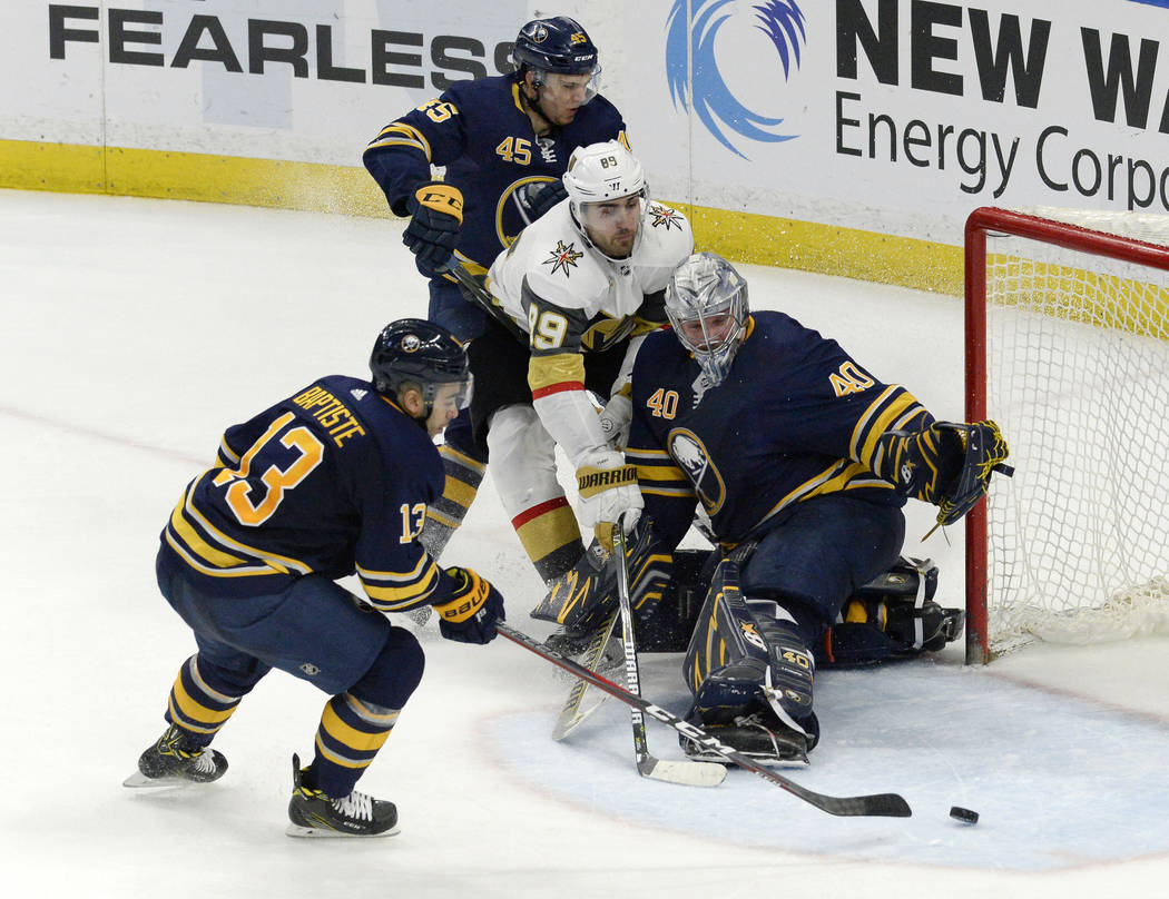 Buffalo Sabres right wing Nicholas Baptiste (13) clears the puck from the the crease Vegas Golden Knights right wing Alex Tuch (89) is shielded by Buffalo Sabres goalie Robin Lehner (40) and defen ...