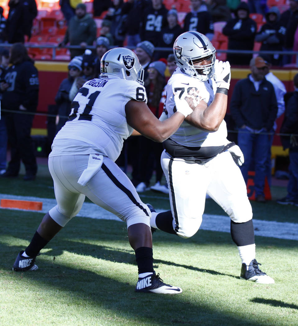 Oakland Raiders center Rodney Hudson (61) and Oakland Raiders defensive tackle Justin Ellis (78) warm up ahead of a NFL game against the Kansas City Chiefs in Kansas City, Mo., Sunday, Dec. 10, 20 ...