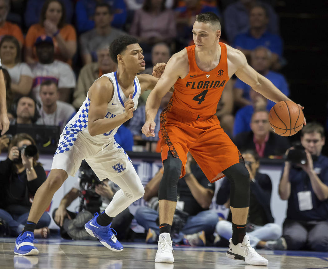 Florida guard Egor Koulechov (4) dribbles against the defense by Kentucky guard Quade Green (0) during the second half of an NCAA college basketball game in Gainesville, Fla., Saturday, March 3, 2 ...