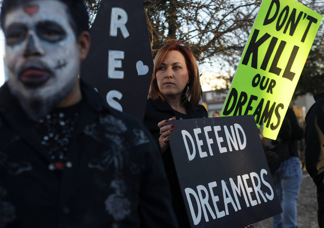 Amy Vilela, center, holds a sign to protest the Trump Administration's attempt to terminate DACA and his continual changes to the TPS program at a parking lot of the Service Employees Internationa ...