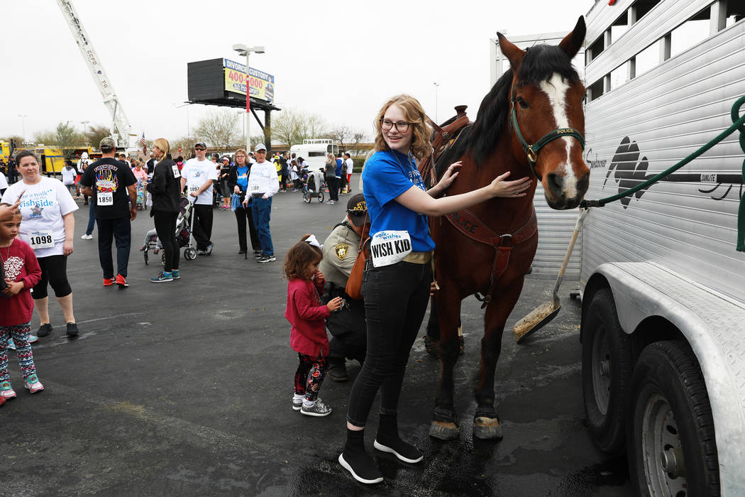 Veronica Beauchamp, 18, pets a horse during the Walk for Wishes event at the Town Square in Las Vegas on Saturday, March 10, 2018. The nationwide Make-A-Wish fundraiser celebrated thousands of wis ...