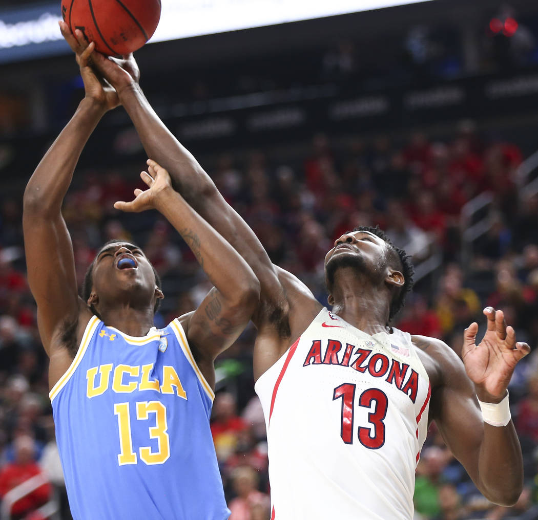 Arizona Wildcats forward Deandre Ayton (13) gets a rebound against UCLA Bruins guard Kris Wilkes (13) during the second half of a semifinal basketball game in the Pac-12 basketball tournament at T ...
