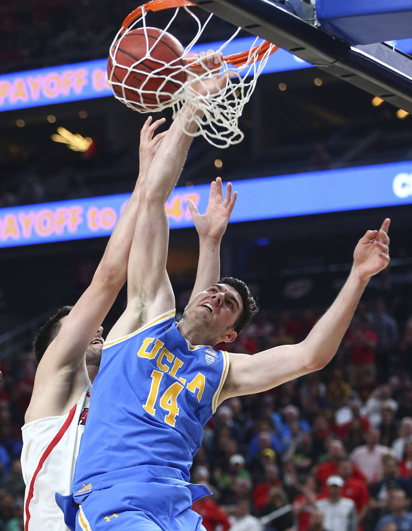 UCLA Bruins forward Gyorgy Goloman (14) dunks in front of Arizona Wildcats center Dusan Ristic during the first half of a semifinal basketball game in the Pac-12 basketball tournament at T-Mobile  ...