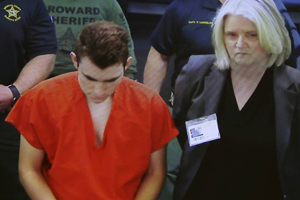 In this image taken from a video monitor, Nikolas Cruz, center, a former student accused of opening fire at Marjory Stoneman Douglas High School on Feb. 14, appears in magistrate court via video c ...