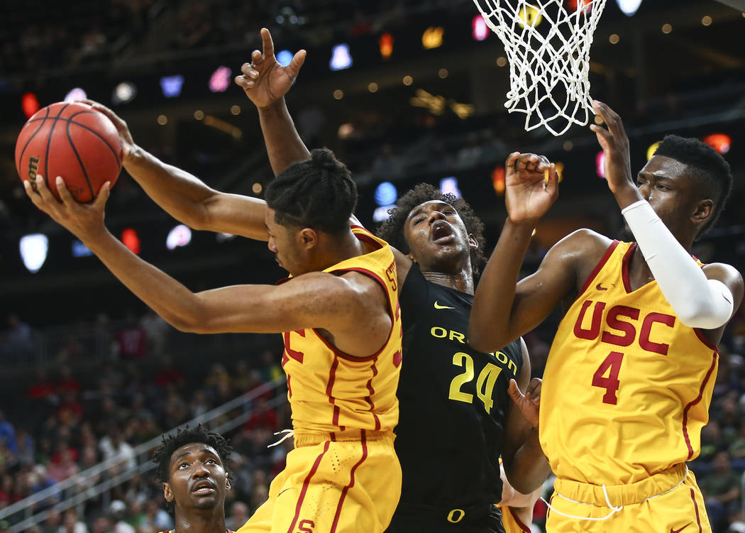 USC Trojans guard Elijah Stewart (30) gets a rebound against Oregon Ducks forward Abu Kigab (24) during the first half of a semifinal basketball game in the Pac-12 basketball tournament at T-Mobil ...