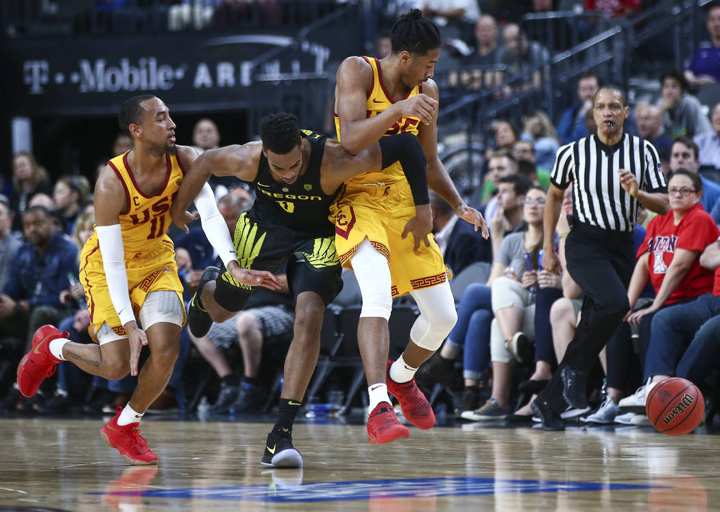 Oregon Ducks forward Troy Brown (0) chases after a loose ball against USC Trojans guards Elijah Stewart, right, and Jordan McLaughlin (11)  during the first half of a semifinal basketball game in  ...