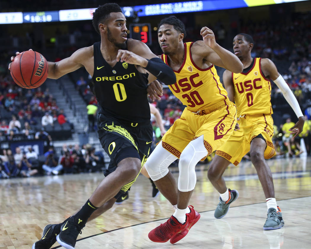 Oregon Ducks forward Troy Brown (0) drives against USC Trojans guard Elijah Stewart (30) during the first half of a semifinal basketball game in the Pac-12 basketball tournament at T-Mobile Arena  ...