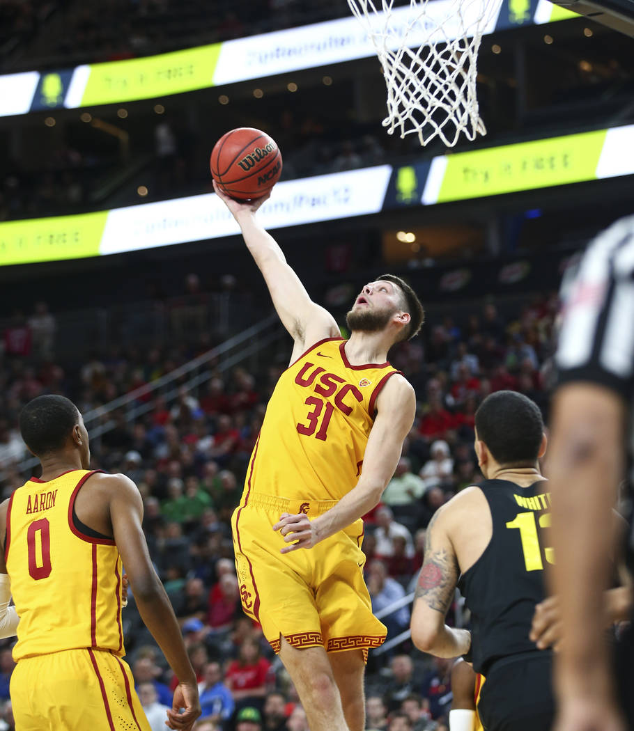 USC Trojans forward Nick Rakocevic (31) gets a rebound over Oregon Ducks forward Paul White (13) during the first half of a semifinal basketball game in the Pac-12 basketball tournament at T-Mobil ...