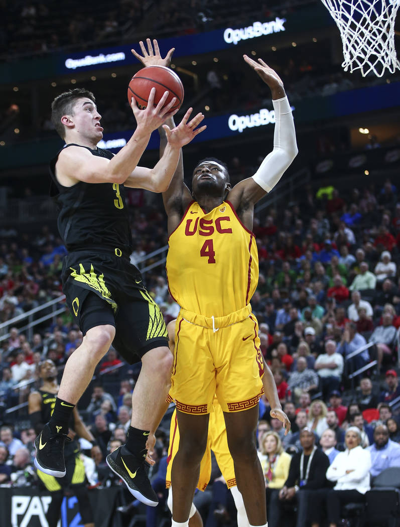 Oregon Ducks guard Payton Pritchard (3) goes to the basket past USC Trojans forward Chimezie Metu (4) during the first half of a semifinal basketball game in the Pac-12 basketball tournament at T- ...
