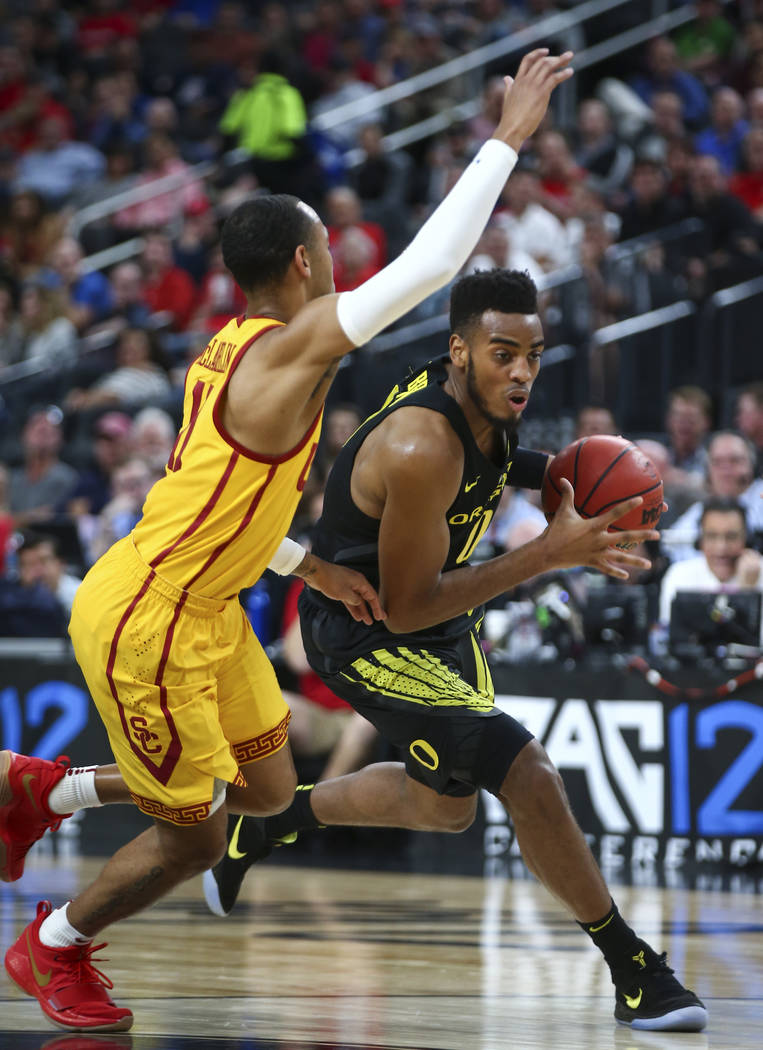 Oregon Ducks forward Troy Brown (0) drives against USC Trojans guard Jordan McLaughlin (11) during the first half of a semifinal basketball game in the Pac-12 basketball tournament at T-Mobile Are ...