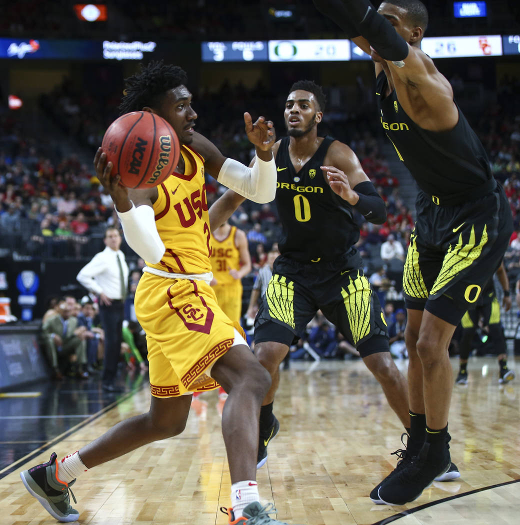 USC Trojans guard Jonah Mathews (2) looks to throw past Oregon Ducks forward Kenny Wooten, right, during the first half of a semifinal basketball game in the Pac-12 basketball tournament at T-Mobi ...