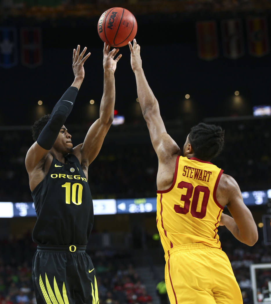 Oregon Ducks guard Victor Bailey Jr. (10) shoots over USC Trojans guard Elijah Stewart (30) during the first half of a semifinal basketball game in the Pac-12 basketball tournament at T-Mobile Are ...