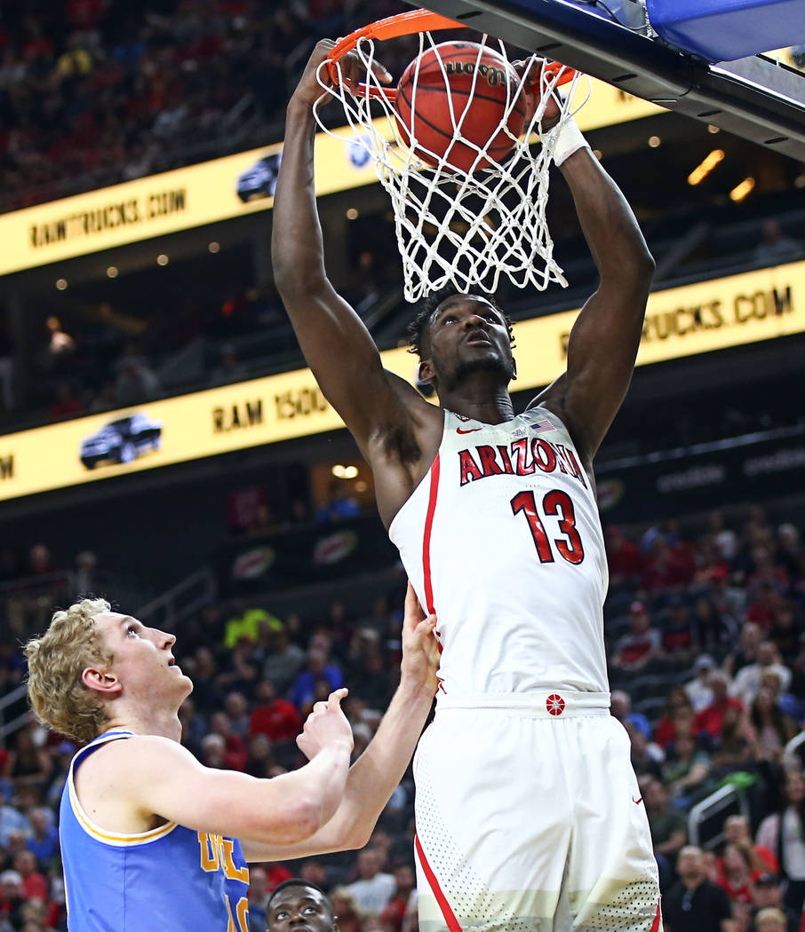 Arizona Wildcats forward Deandre Ayton (13) dunks over UCLA Bruins center Thomas Welsh (40) during the second half of a semifinal basketball game in the Pac-12 basketball tournament at T-Mobile Ar ...