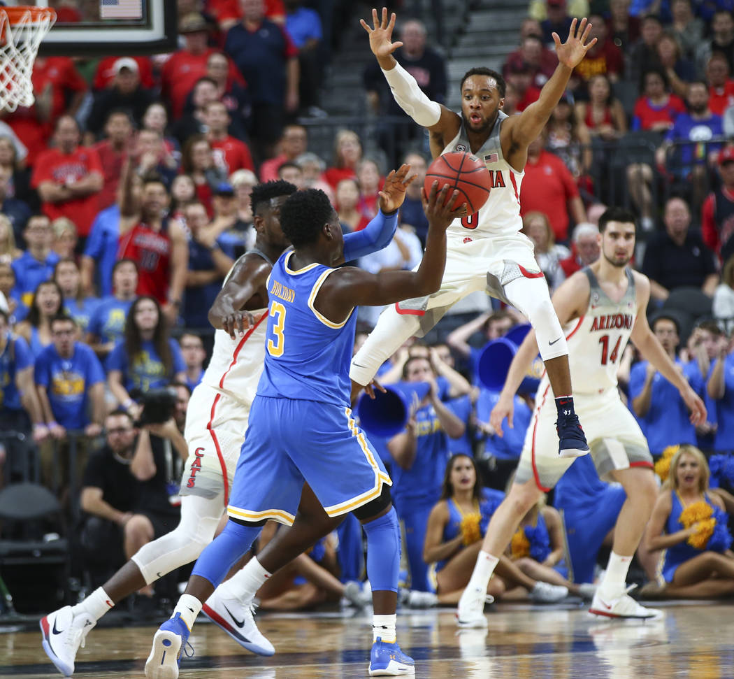 UCLA Bruins guard Aaron Holiday (3) looks to pass the ball as Arizona Wildcats guard Parker Jackson-Cartwright, upper right, defends during overtime in a semifinal basketball game in the Pac-12 ba ...