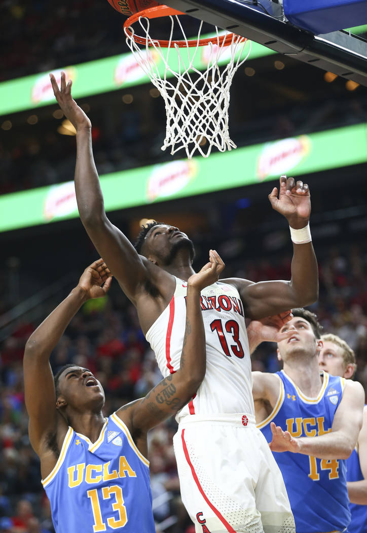 Arizona Wildcats forward Deandre Ayton (13) sends up a shot between UCLA Bruins guard Kris Wilkes (13) and forward Gyorgy Goloman (14) during the second half of a semifinal basketball game in the  ...