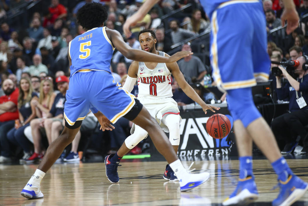 Arizona Wildcats guard Parker Jackson-Cartwright (0) looks to get around UCLA Bruins guard Chris Smith (5) during the second half of a semifinal basketball game in the Pac-12 basketball tournament ...
