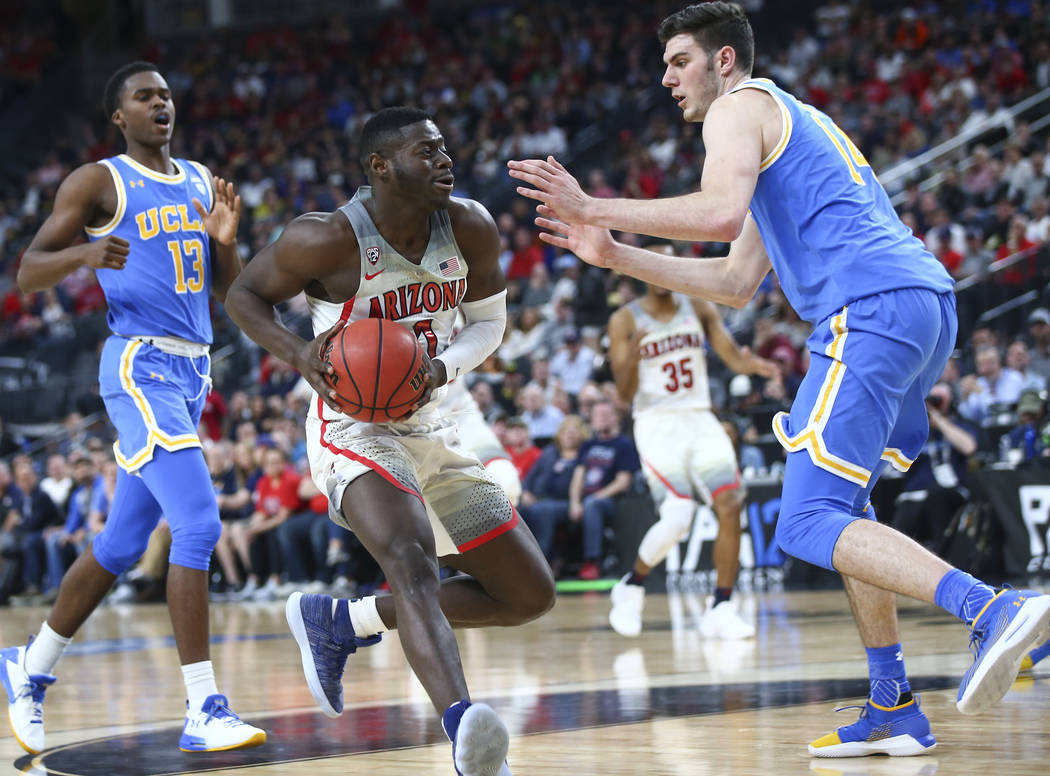 Arizona Wildcats guard Rawle Alkins (1) drives as UCLA Bruins forward Gyorgy Goloman (14) defends during the second half of a semifinal basketball game in the Pac-12 basketball tournament at T-Mob ...