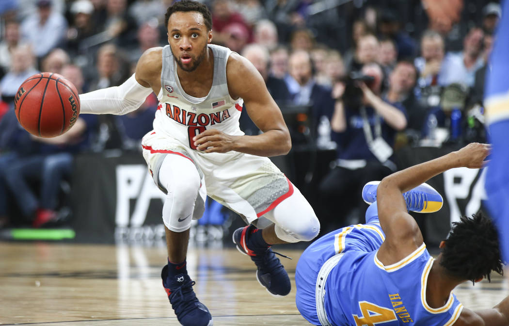 Arizona Wildcats guard Parker Jackson-Cartwright (0) drives past UCLA Bruins guard Jaylen Hands (4) during the second half of a semifinal basketball game in the Pac-12 basketball tournament at T-M ...
