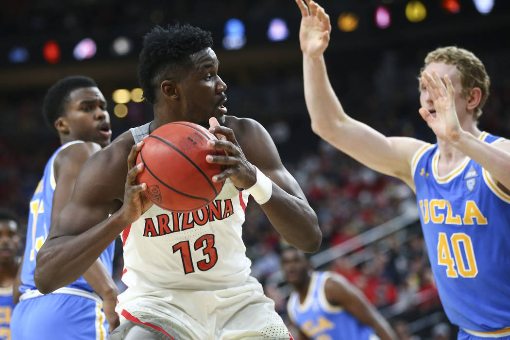Arizona Wildcats forward Deandre Ayton (13) looks to get past UCLA Bruins center Thomas Welsh (40) during the second half of a semifinal basketball game in the Pac-12 basketball tournament at T-Mo ...