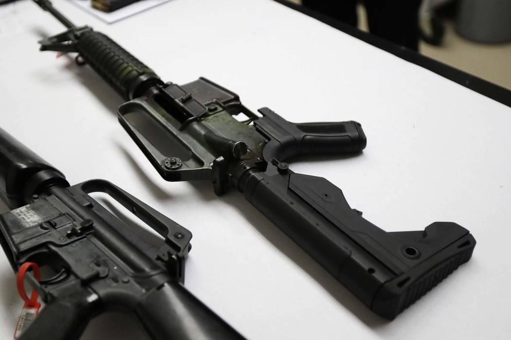 A semi-automatic rifle at right that has been fitted with a so-called bump stock device to make it fire faster sits on a table at the Washington State Patrol crime laboratory in Seattle, Jan. 11,  ...