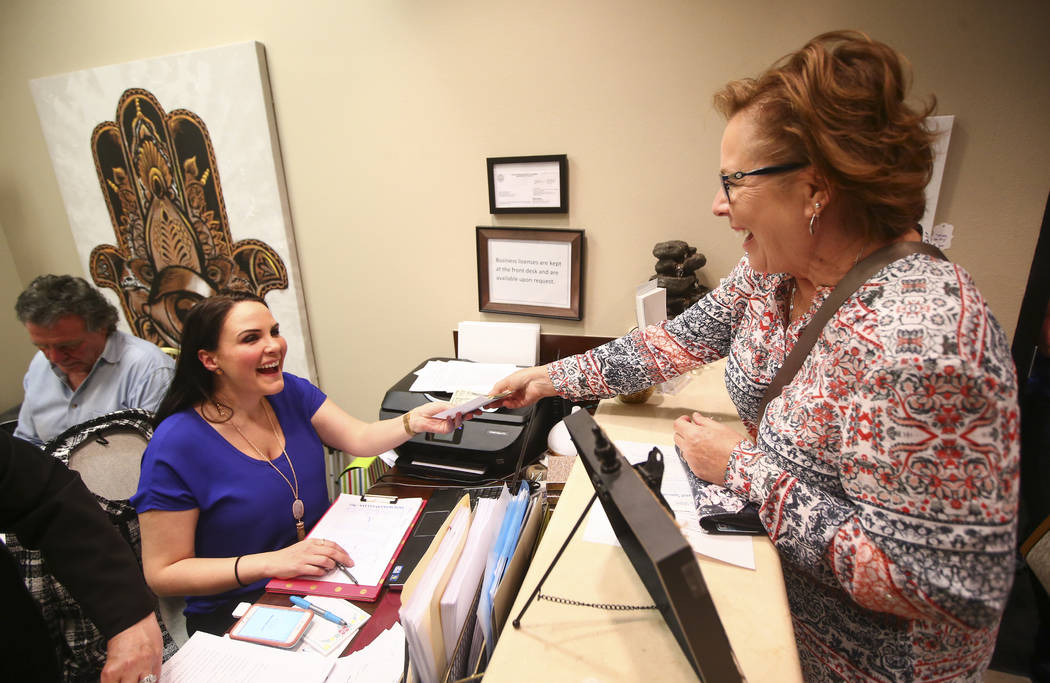 Owner Dallisa Hocking, left, assists customer Karen Artus during the grand opening event at Spirit & Spark, which offers services such as from psychic readings, yoga and meditiation, in Hender ...