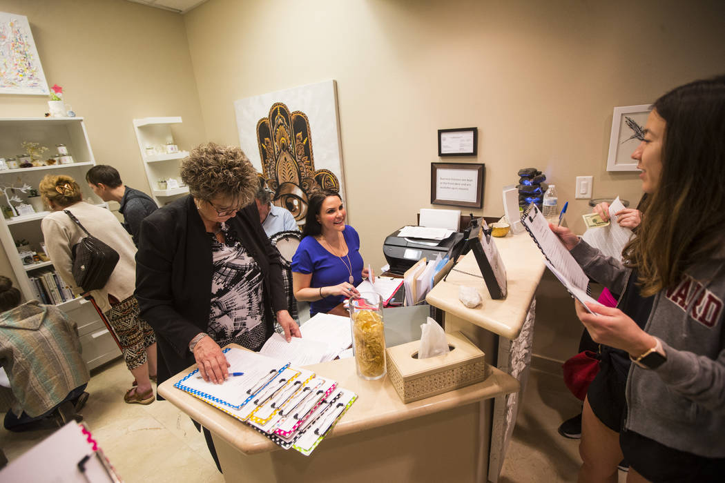 Owner Dallisa Hocking, center, assists customers during the grand opening event at Spirit & Spark, which offers services such as from psychic readings, yoga and meditiation, in Henderson on Sa ...