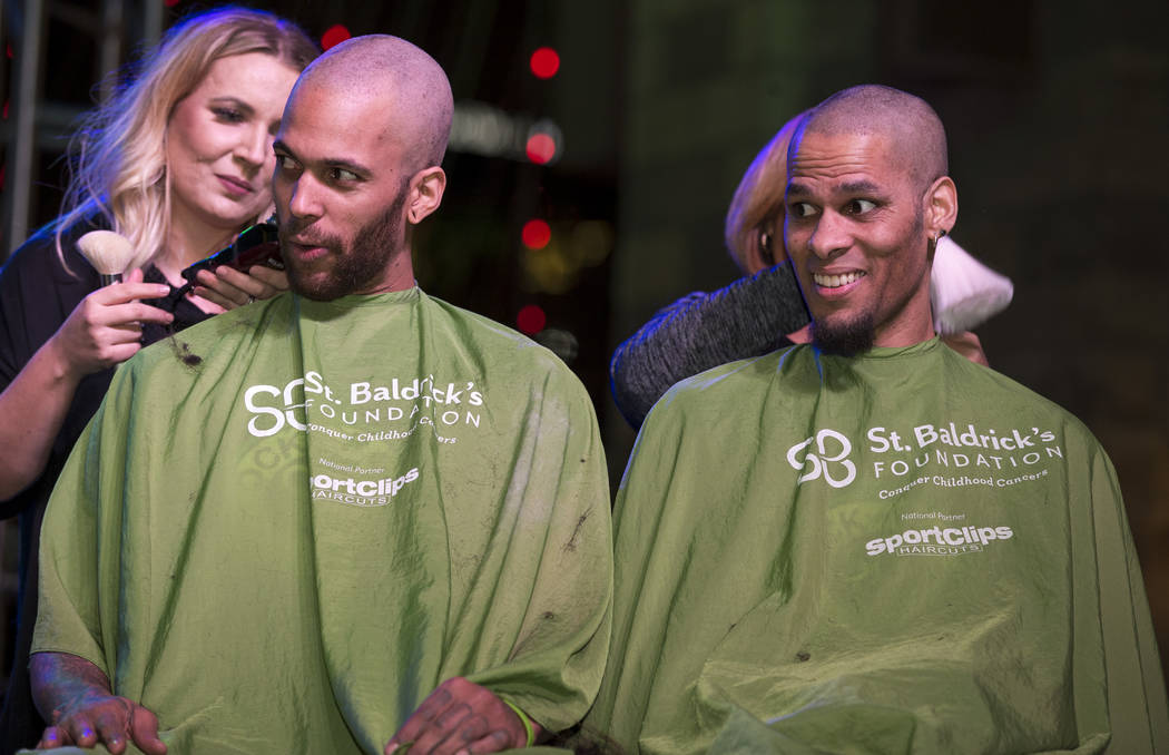 Brothers Dan, left, and Greg Murrell, of Las Vegas, shave their heads during a St. Baldrick's head-shaving event to raise money for childhood cancer research outside the New York-New York on the L ...