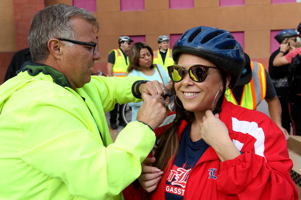 Ron Floth, bicycle and community outreach coordinator for the Regional Transportation Commission, secures a helmet for Krissy Bashaw at an RTC Bike Share station near the Clark County Government C ...