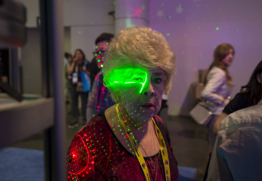 Patricia Bown of Minnesota visits the New Star Wholesale Inc. sign and laser projection booth during the ASD Market Week Trade Show at the Las Vegas Convention Center on Sunday, March 11, 2018. Ri ...