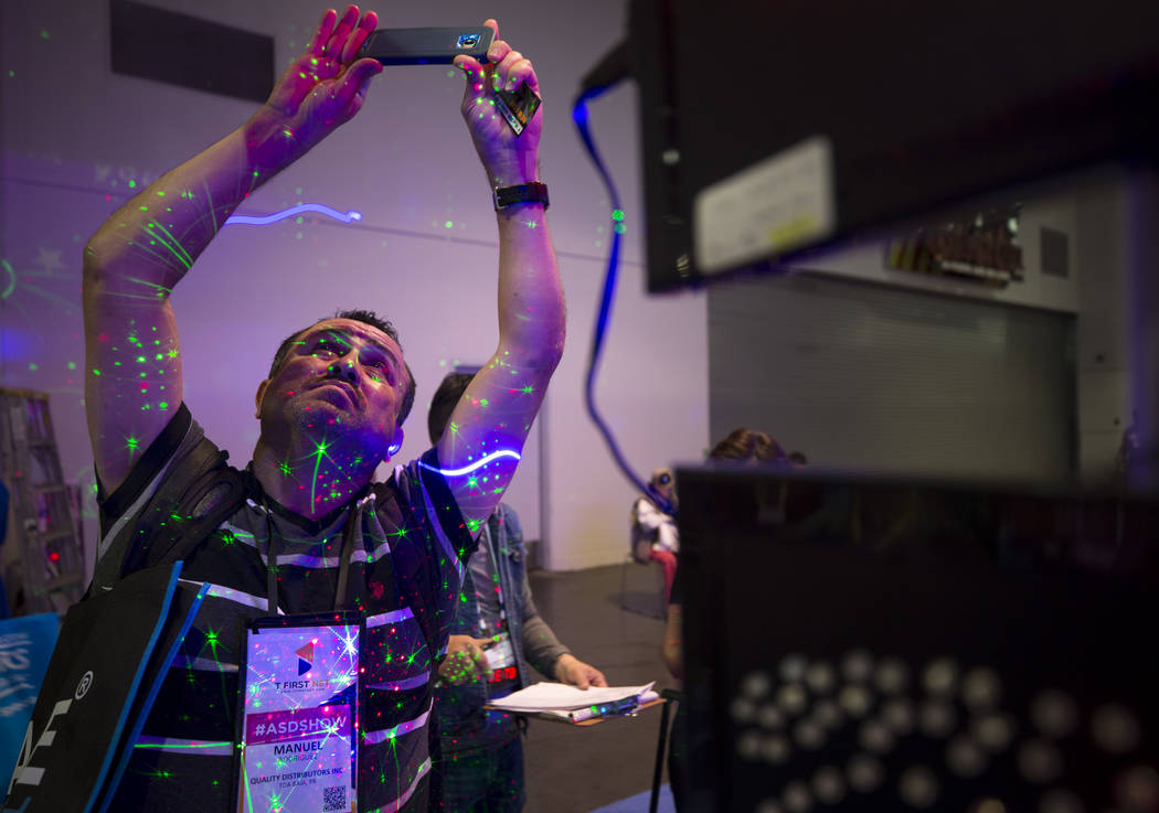 Manuel Rodriguez of Puerto Rico snaps a photo as he visits the New Star Wholesale Inc. sign and laser projection booth during the ASD Market Week Trade Show at the Las Vegas Convention Center on S ...