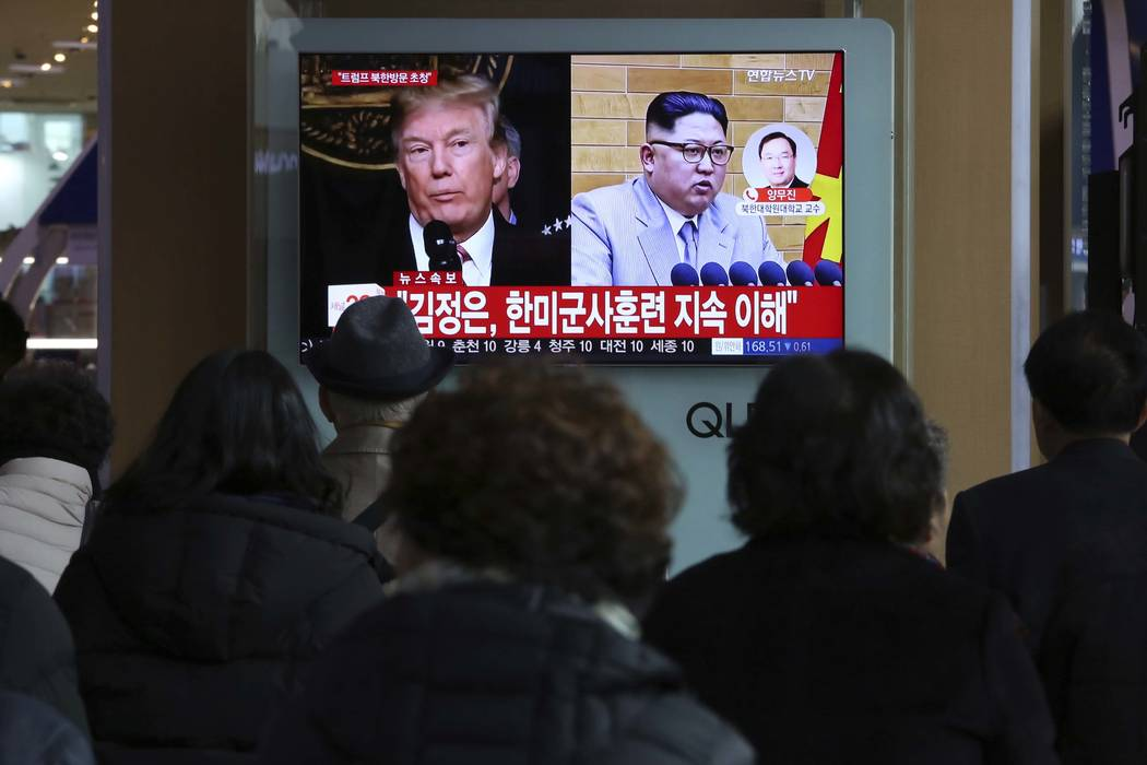People watch a TV screen showing North Korean leader Kim Jong Un and U.S. President Donald Trump, left, at the Seoul Railway Station in Seoul, South Korea, Friday, March 9, 2018. (AP Photo/Ahn You ...