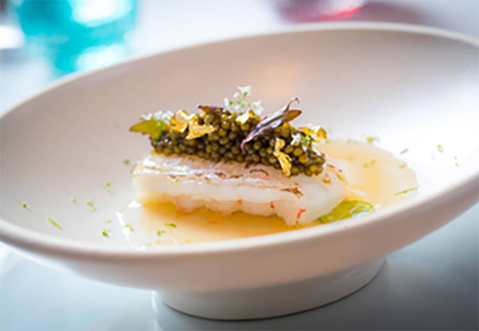 Langoustine topped with Osetra caviar and gold leaf. Guy Savoy