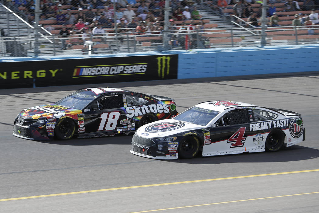 Monster Energy NASCAR Cup Series driver Kevin Harvick (4) passes Kyle Busch (18) on lap 131 during a NASCAR Cup Series auto race on Sunday, March 11, 2018, in Avondale, Ariz. (AP Photo/Rick Scuteri)
