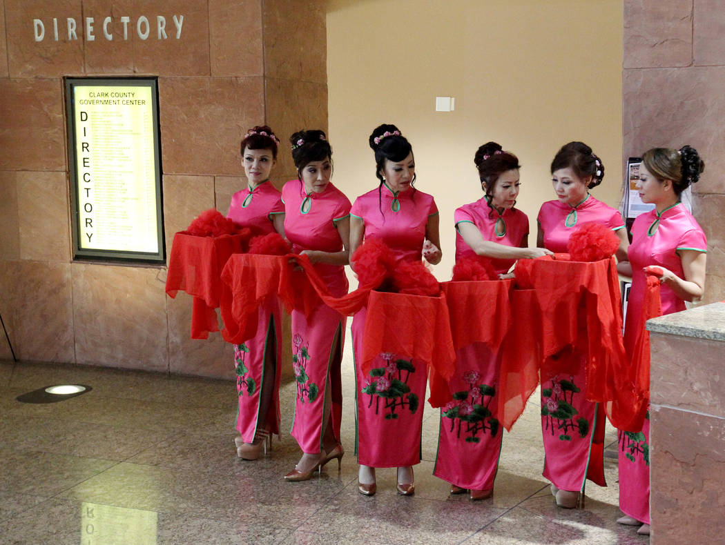 Hostesses prepare a red ribbon to be cut for the opening of ÒThe Story of Chinese InkÓ exhibit in the Rotunda Gallery at the Clark County Government Center in Las Vegas Monday, March 5,  ...