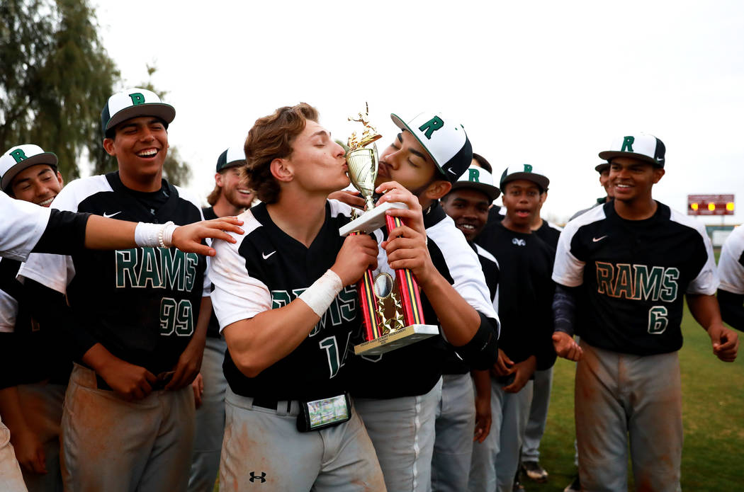 Rancho Rams' Joseph Walls (14) and Carlos Hernandez (25) kiss the trophy after beating the Arbor View Aggies at Desert Oasis High School in Las Vegas on Saturday, March 10, 2018. The Rams won 10-4 ...