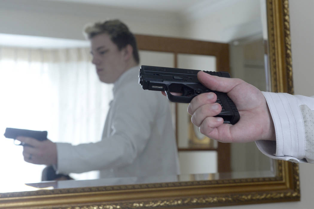 Twenty-year-old Jared Larson, carries a concealed firearm with a new provisional state permit. Larson pictured on March 1, 2018 in his Centerville, Utah, home. He wears his 9mm handgun in a holste ...