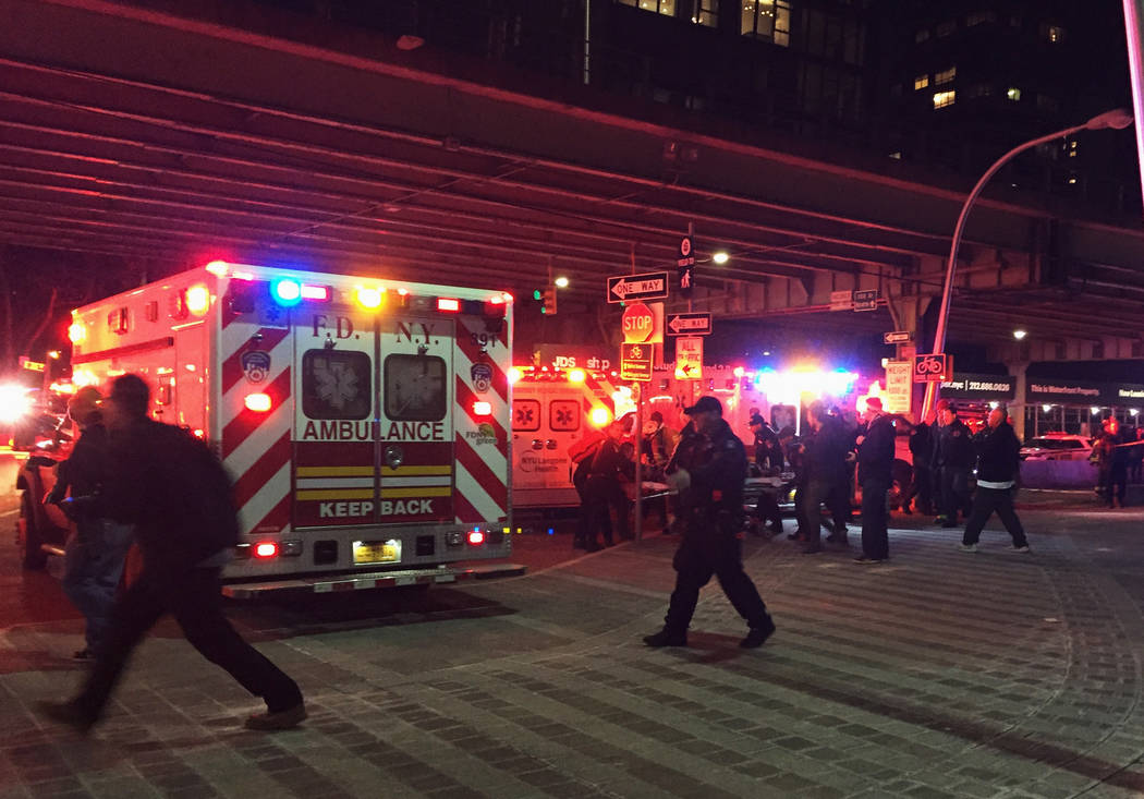 First responders carry a person to an ambulance after a helicopter crashed into the East River along New York on Sunday, March 11, 2018. A Federal Aviation Administration spokeswoman said Sunday t ...