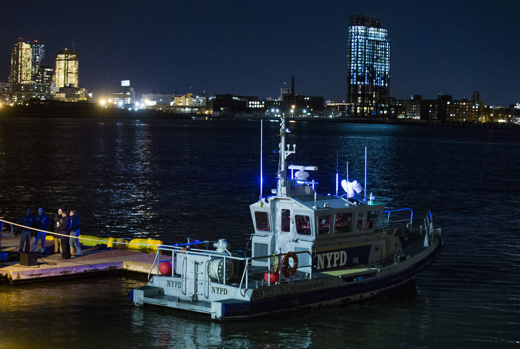 Yellow buoys that a New York police officer said are suspending a helicopter that crashed on the East River float next to a NYPD police boat at a pier in New York on Sunday, March 11, 2018. The he ...