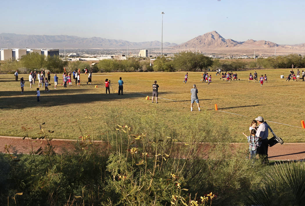 Children play flag football on the field behind Reunion Trails Park Thursday, Oct. 26, 2017, in Henderson. The city of Henderson and the Clark County District are disagreeing over a new proposed s ...