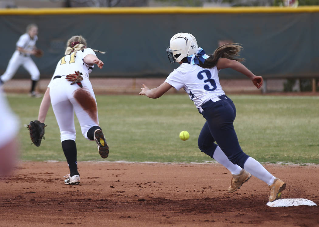Centennial's Natasha Lawrence (3) looks to steal third base past Faith Lutheran's Maggie Whipple (11) during a softball game at Faith Lutheran in Las Vegas on Tuesday, March 13, 2018. Centennial w ...