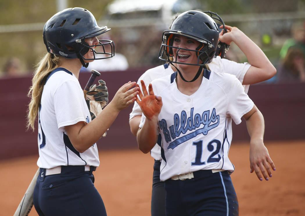 Centennial's Abby Hanley (12) celebrates her run with Centennial's Seanna Simpson (5) during a softball game at Faith Lutheran in Las Vegas on Tuesday, March 13, 2018. Centennial won 14-1. Chase S ...